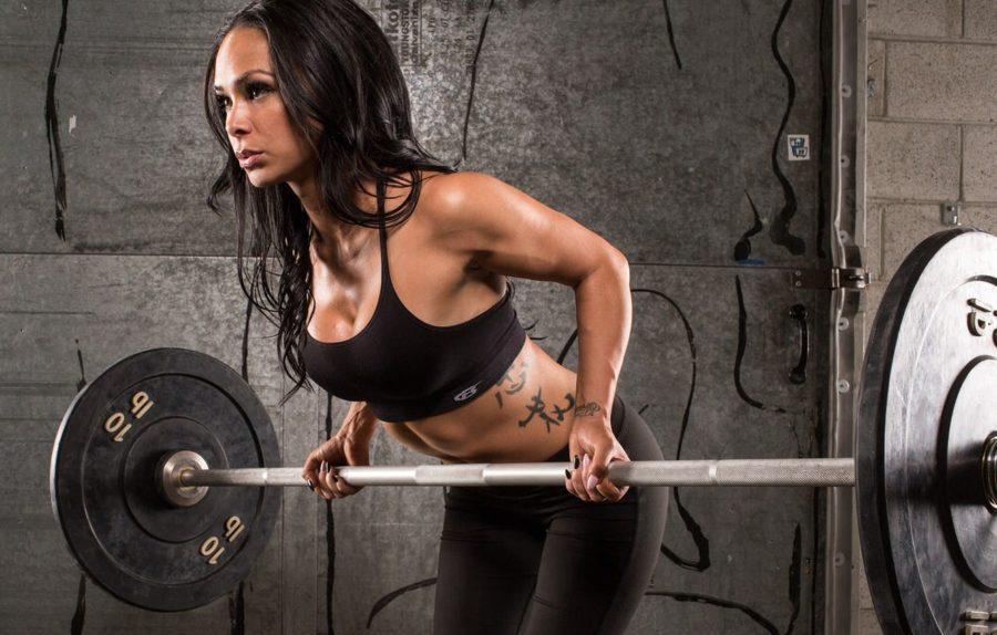 Стройная девушка выполняет тягу штанги обратным хватом стоя в наклоне/. Программа тренировок на тонус мышц