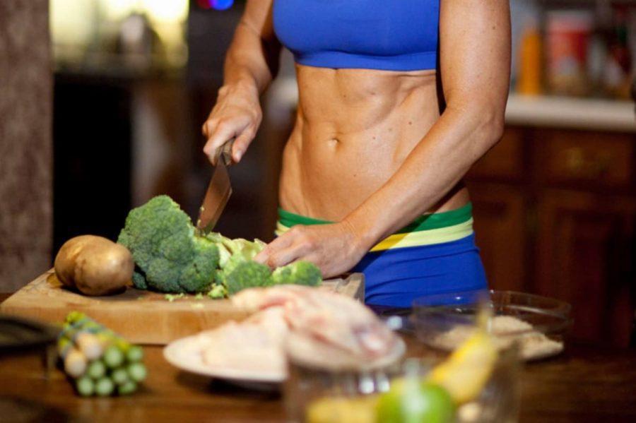 Спортивная девушка на кухне готовит
